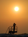 Military Sentry in Front of Sunset. Military sentry in front of a setting sun Royalty Free Stock Image