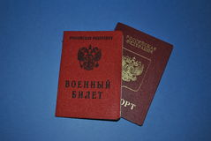 Military service in Russia. The Russian passport and a military ID on a blue background stock photos