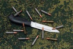Military sheathless knife and cartridges on camouflage backround Royalty Free Stock Photo