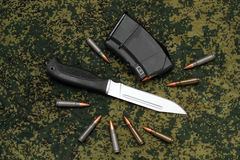 Military sheathless knife, magazine and cartridges on camouflage backround Stock Photography