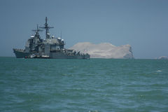 Military ship in Peru. With a huge rock in the green water behind the grey ship Royalty Free Stock Photos