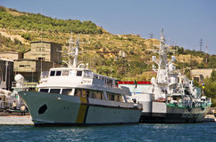 Military ship and yacht  in bay Royalty Free Stock Image