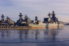 Military squadron in the port. Military ships with sophisticated navigation equipment are in the roadstead. Cold sea, north, severe climate. The water is Royalty Free Stock Photo