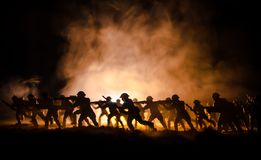 Military silhouettes of soldiers against the backdrop of dark foggy sky. Battle scene with explosion and burning clouds behind fig Stock Photos