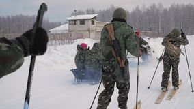 Military on skis with a guns. Clip. Group of soldiers on skis in the woods.  stock video footage