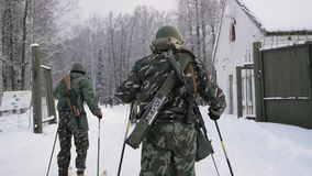 Military on skis with a guns. Clip. Group of soldiers on skis in the woods.  stock footage