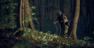 Military Soldier in Action. At Night in the Forest Area. Night Time Military Mission. Panoramic Photo. Soldier with Assault Rifle with Flashlight Between Trees royalty free stock photo