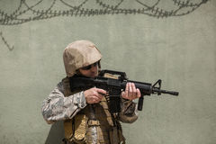 Military soldier aiming with a rifle against concrete wall. In boot camp stock images