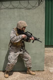 Military soldier aiming with a rifle against concrete wall. In boot camp royalty free stock image