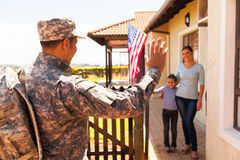 Military soldier arriving home. With family welcoming him stock images