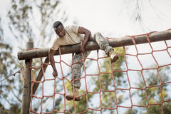 Military soldier climbing net during obstacle course Stock Image