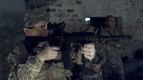 Military soldier firing with riffle during military training