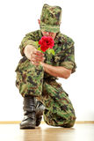 Military soldier kneeling holding red rose Stock Photography