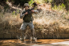 Military soldier with rifle jumping in water. In boot camp Stock Images