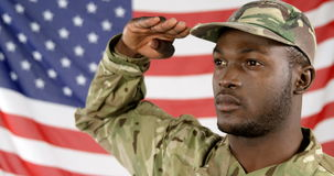 Military soldier saluting. Against the US flag background 4k stock video
