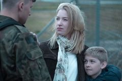 Military soldier saying goodbye. To wife and son stock photography