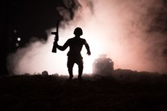 Military soldier silhouette with gun. War Concept. Military silhouettes fighting scene on war fog sky background, World War Soldie. R Silhouette Below Cloudy Stock Image