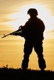 Military soldier silhouette with machine gun. Military. soldier silhouette in uniform with machine gun or assault rifle at summer evening sunset Stock Photo