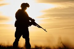 Military soldier silhouette with machine gun. Military. soldier silhouette in uniform with machine gun or assault rifle at summer evening sunset Stock Images
