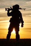 Military soldier silhouette with machine gun. Military. soldier silhouette in uniform with machine gun or assault rifle at summer evening sunset Stock Image