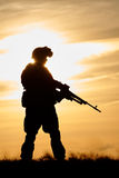 Military soldier silhouette with machine gun. Military. soldier silhouette in uniform with machine gun or assault rifle at summer evening sunset stock photos