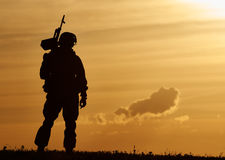 Military soldier silhouette with machine gun Stock Photos