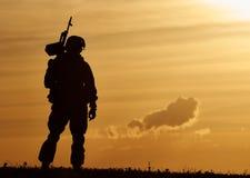 Military soldier silhouette with machine gun. Military. soldier silhouette in uniform with machine gun or assault rifle at summer evening sunset Stock Photos
