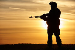 Military soldier silhouette with machine gun. Military. soldier silhouette in uniform with machine gun or assault rifle at summer evening sunset Royalty Free Stock Images
