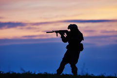 Military soldier silhouette with machine gun. Military. soldier silhouette in uniform with machine gun or assault rifle at summer evening sunset Stock Photography