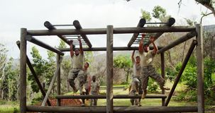 Military soldiers climbing monkey bars 4k. Military soldiers climbing monkey bars at boot camp 4k stock video footage