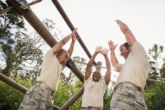Military soldiers with hands stacked during obstacle training Stock Image