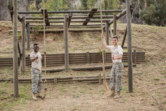 Military soldiers showing thumbs while holding rope during boot camp training Royalty Free Stock Images