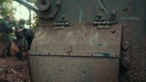 Military soldiers with weapon standing on background army tank. At battle field. Soldiers protecting tank during military operation stock footage