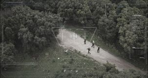 Surveillance drone camera view of terrorist squad walking with weapons. Military surveillance drone view of terrorists walking through a forest stock footage