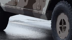 Military SUV. Camouflaged military 4x4 wheels drive traction, close-up shot, slowly passing stock video footage
