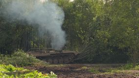Military tank breaks down green trees to build road in forest for fight enemy. Military tank breaks down green trees to build road in forest. Armored vehicle on stock footage