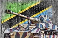Military tank with concrete Tanzania flag stock photography