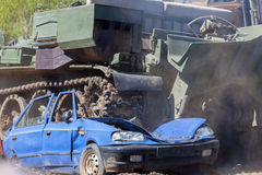 Military tank crushes a blue car Stock Photos