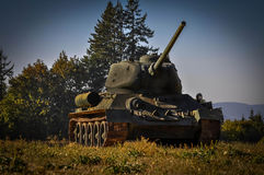 Military tank. Sitting on the edge of the woods stock photography
