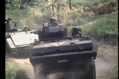 Military tanks and foot soldiers advancing down dirt road stock video