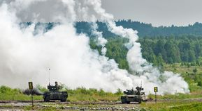 Military tanks hide behind smoke screen Stock Photos