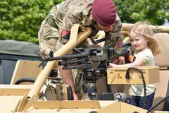 Military Tattoo COLCHESTER ESSEX UK 8 July 2014: Small Girl being shown gun. By soldier royalty free stock photography