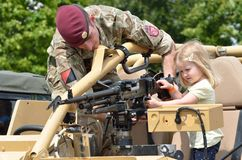 Military Tattoo COLCHESTER ESSEX UK 8 July 2014: Small Girl being shown machine gun. By soldier stock photo