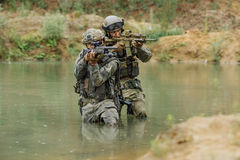Military team crossing the river under fire Royalty Free Stock Photo