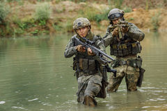 Military team crossing the river under fire Royalty Free Stock Photos