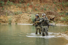Military team crossing the river under fire Royalty Free Stock Image
