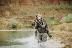 Military team crossing the river under fire Stock Photography