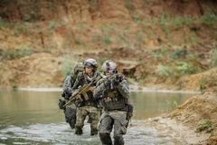 Military team crossing the river under fire Royalty Free Stock Images
