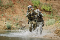 Military team crossing the river under fire Royalty Free Stock Photography
