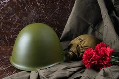 Military things and red flowers on a marble slab, a monument of battles Royalty Free Stock Photography